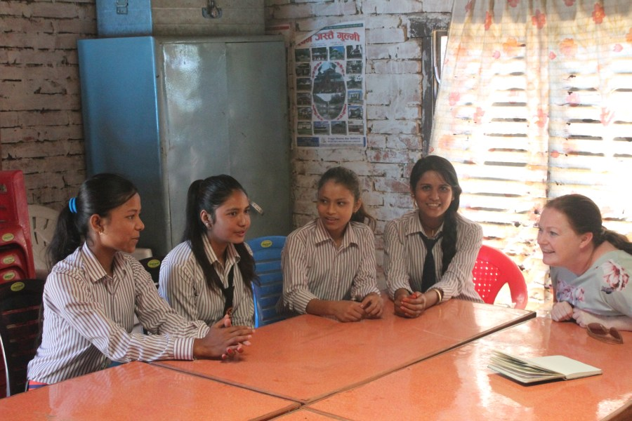 Urmila, Nurita, Deepa and Manisha sit and join in conversation in the classroom.