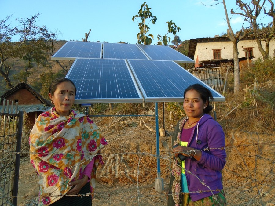 two women standing next to a solar array