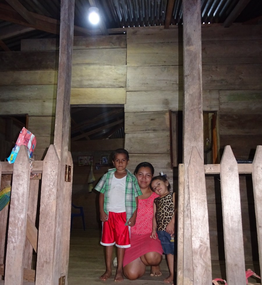 Maricela and her children outside their home