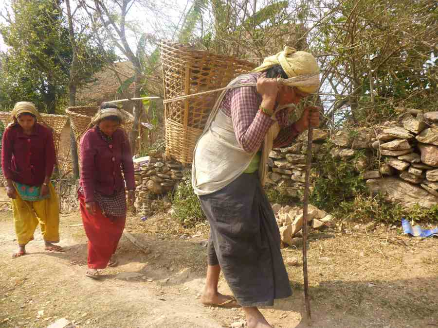 Women carrying heavy loads back to their village
