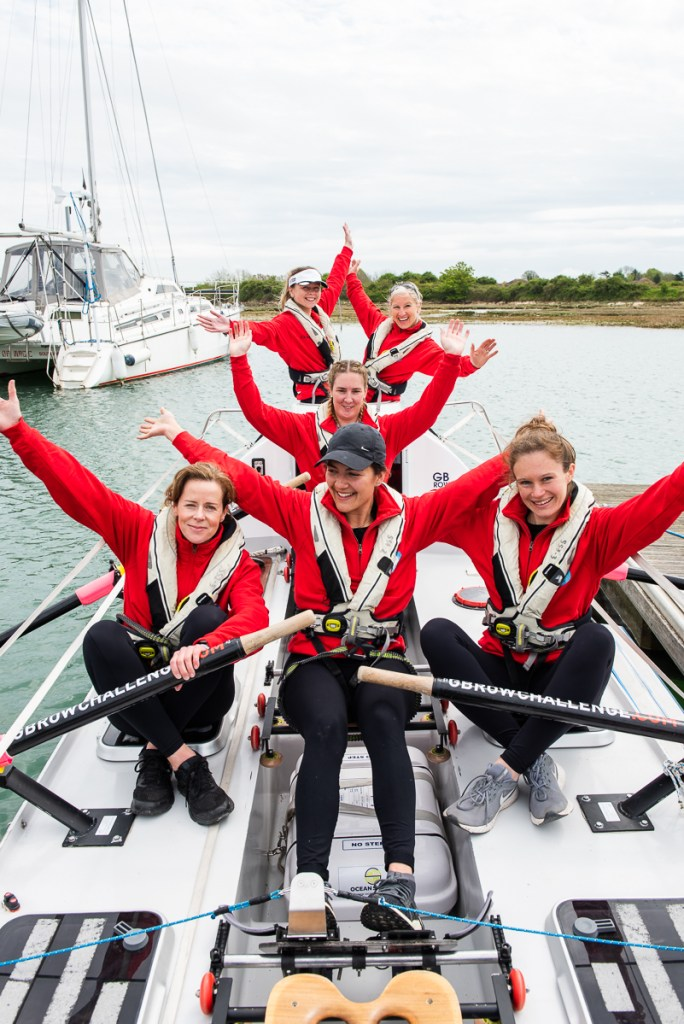 The All Systems Row team: all six ladies are sitting in their rowing boat, on the water, smiling and with their arms raised in celebration.