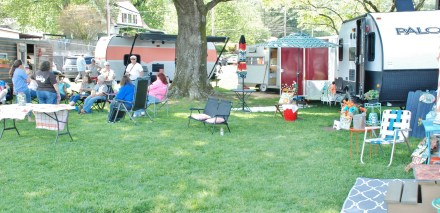 Sisters on the Fly relax in the shade of a convenient tree as Festival-goers tour their vintage campers.