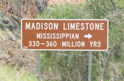 Signs in the Bighorn National Forest identify the age and type of stone formation seen nearby.