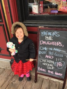 father daughter dance - daughter by restaurant sign