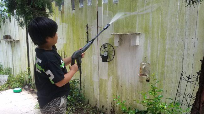 高圧洗浄機で塀のこけ掃除をしている様子