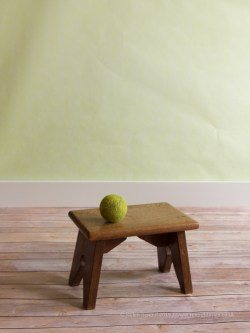 A fake backdrop and floor lit with window light.