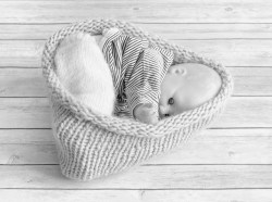 A hand knitted baby nest on floor boards in monochrome