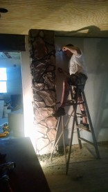 Adding rock to the chimney on the inside of our 100 year old farmhouse, here Joe is grouting.