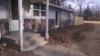 Adding rock to cover old stucco on the front of our 100 year old farm house. Here it is compeltely finished.