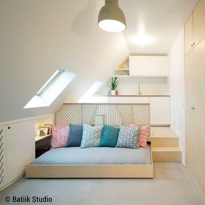 Lit escamotable sous l'estrade qui accueille la cuisine, par Batiik Studio