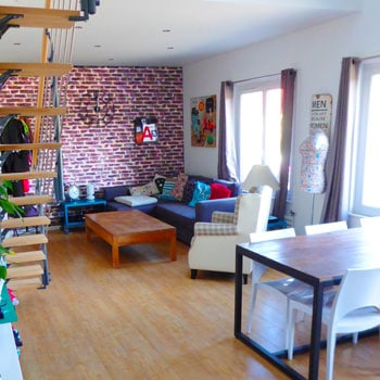 Le T2 défraîchi s'est transformé en un duplex de 105 m² au sol, 76 m² loi Carrez, décoré dans un style loft, avec une mezzanine ouverte au-dessus du séjour
