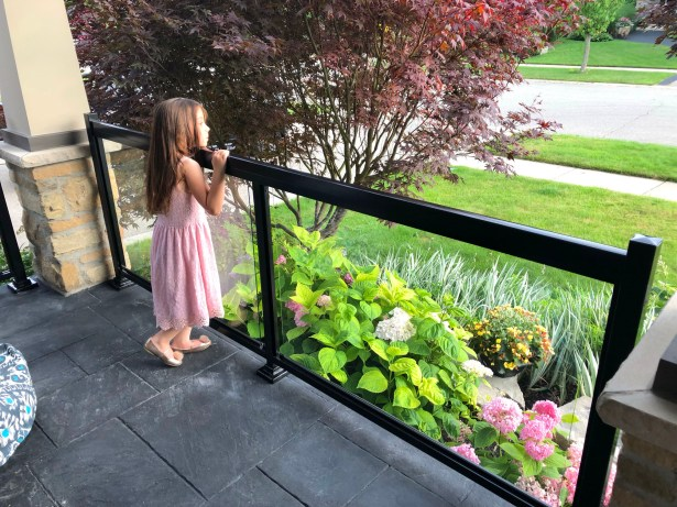 Renaissance Rail young girl overlooking aluminum and glass railing