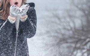 ダウンを着た女性が雪の中で立っている
