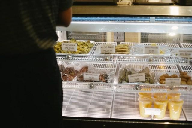 crop person choosing desserts in bakery