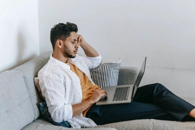 ethnic man browsing laptop at home