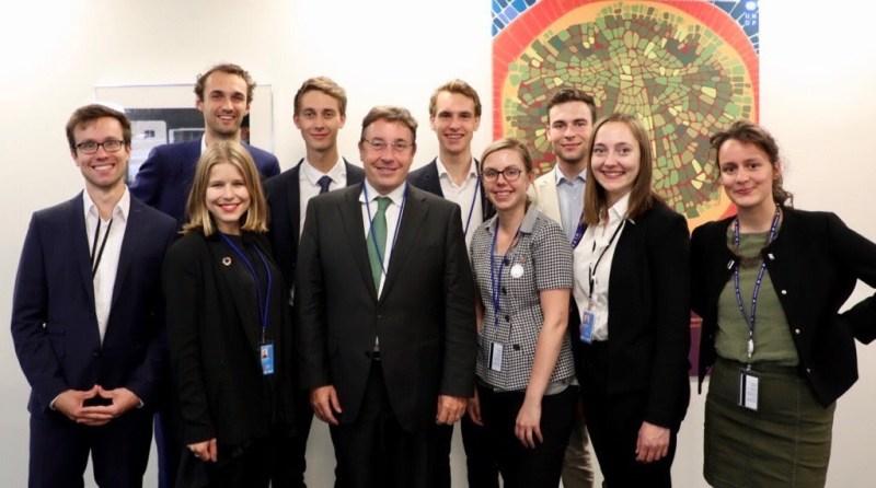 Alla ungdomsdelegater står på rad med Achim Steiner i mitten. I bakgrunden en vit vägg med en stor, grön tavla.