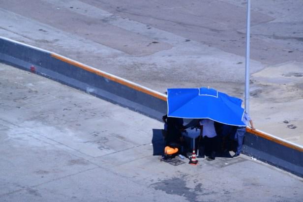 Des hommes sous un parasol sur le quai