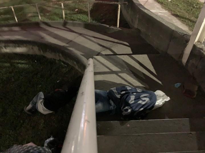 Personas duermen al pie del puente frente a la terminal de buses de San Pedro Sula, Honduras. Foto: Dennis Arita