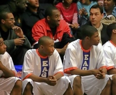 Kobe Bryant (center in red) and his then agent and now Los Angeles Lakers General Manager Rob Pelinka (to his left) watch the Eagles against St. Pius X in 2007. Eagles on the bench include (l-r) Allen Moorer, Steve Lattimore and Antonio Wilson. (Courtesy photo)