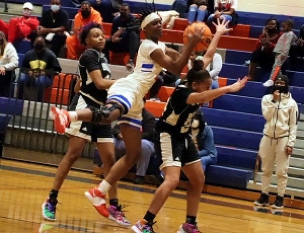 Columbia's Nia Anderson (4) brings down a rebound between Butler's Tamesha Slater (21) and Markera Tarver (24) during Butler's 56-55 win in the Class 2A girls' quarterfinal game at Columbia. (Photo by Mark Brock)