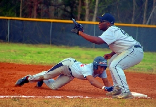 Martin Luther King's Leigh Allen dives safely back to first as Lithonia first baseman Wesley Covert waits for a throw during the Lions 11-4 win at Lithonia. (Photo by Mark Brock