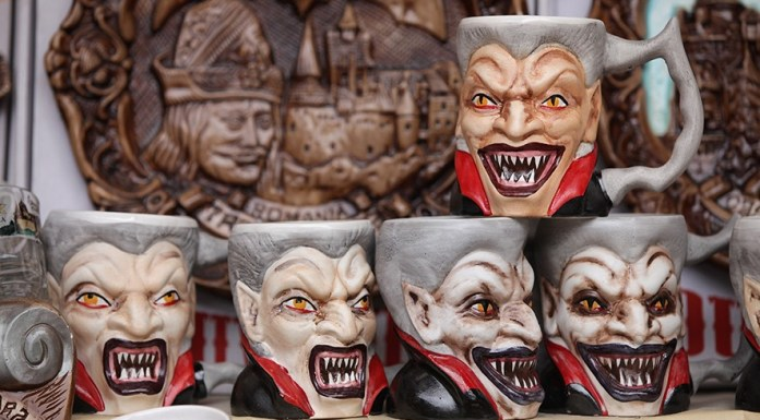 """BRAN, ROMANIA - MARCH 10: Mugs bearing a rendition of Dracula are displayed at a souvenir shop at Bran Castle, famous as """"Dracula's Castle,"""" on March 10, 2013 in Bran, Romania. Bran Castle's reputation as the supposed home to Dracula corresponds little with Bram Stoker's novel, nor did Vlad Tepes, the sadistic 15th-century Wallachian prince, ever live there. Nevetheless the castle retains the myth and tourists flock there in large numbers. Bran Castle, along with the mountainous region of southern Transylvania, which is home to Saxon fortified towns and churches, are among the asssets the Romanian government hopes will bring increasing numbers of tourists to the country. Both Romania and Bulgaria have been members of the European Union since 2007 and restrictions on their citizens' right to work within the EU are scheduled to end by the end of this year. However Germany's interior minister announced recently that he would veto the two countries' entry into the Schengen Agreement, which would not affect labour rights but would prevent passport-free travel. (Photo by Sean Gallup/Getty Images)"""