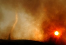 405313 01: A wildfire-induced tornado of hot ash dances across a ridgetop as the sun sets May 13, 2002 near Rancho Santa Margarita, CA. The fire consumed about 1,100 acres in less than six hours and seriously threatened 200 homes. Because the region is experiencing what may be the dryest season on record, native vegatation has a very low moisture content causing the official fire season to begin about six weeks earlier than usual. An extremely dangerous fire season is widely predicted for southern California this year. (Photo by David McNew/Getty Images)