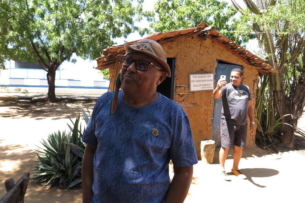 Legenda: Joquinha Gonzaga, sobrinho de Luiz Gonzaga, com réplica ao fundo da casa de reboco que serviu de inspiração a uma de suas músicas Foto: FOTO: ANTÔNIO RODRIGUES