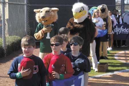 mascots from area schools join players as the national anthem is sung on the Northside Youth Organization's Opening Day ceremony at Chastain Park in Buckhead on March 16.