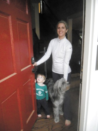 Melissa Pate, son Hudson, age 2, and Pookie answer the door at their home in the Redfield subdivision in Dunwoody. Pate grew up in the neighborhood and moved back to raise her own kids there.
