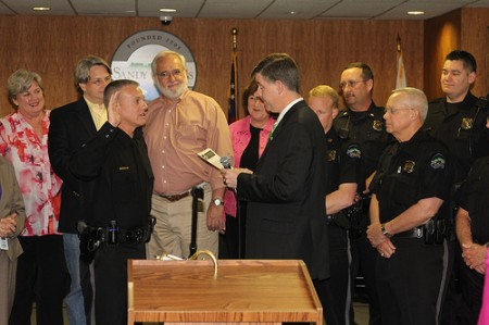 Sandy Springs City Manager John McDonough, front right, swears in Kenneth DeSimone as the city's new Police Chief. In the Background, left to right, are Councilwoman Dianne Fries, Councilman Gabriel Sterling, Councilman Tibby DeJulio, and members of the Sandy Springs Police Department.