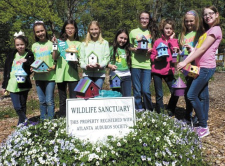 Girl Scouts from Troop 29430 at Our Lady of the Assumption Elementary School show off birdhouses they decorated as a service project for the Dunwoody Community Garden. From left, Abby Johnson, Bella Cabibi, Lauren Kim, Francesca Walker, Katie Wojna, Lauren Natsch, Ava Massey, Tegan Siksta and Hallye Loeffler.
