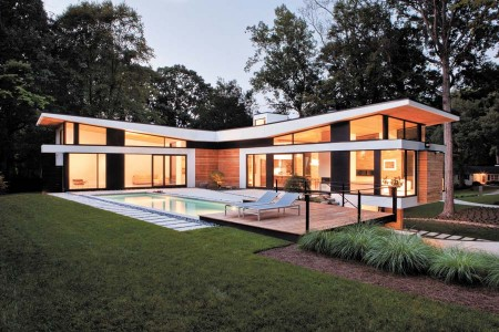 The Sarvis residence in Buckhead, designed by Dencity, was constructed with local stone, cypress, European stucco and commercial glass. The T-shaped plan creates a private area in the back that contains an outdoor patio and pool. The Earthcraft-certified home also has a distinct roof form, which makes it appear to be lifting off the house.