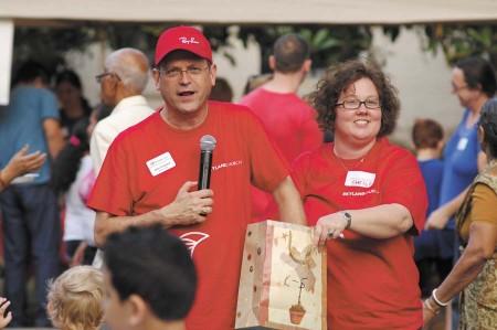 Church Pastor John Freeland, left, and Sheila de la Cruz, give away children's books.