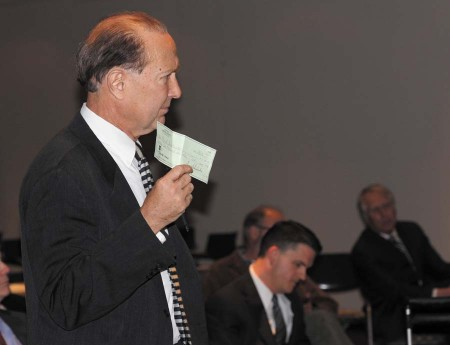 Pink Pony attorney Aubrey Villines offers Brookhaven City Council a check for $25,000, the quarterly licensing fee the club now pays DeKalb County.