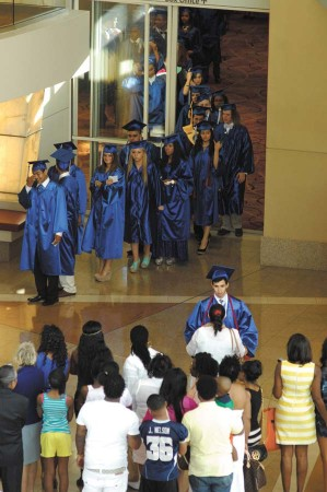 Graduates wait in line as family and friends look on.