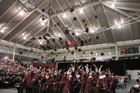 Caps are tossed into the air in the school's main gym after graduation.