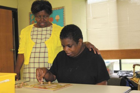 Verona Durden, left, helps Valentina Campbell work on a puzzle at the DeKalb Services Center in Brookhaven.