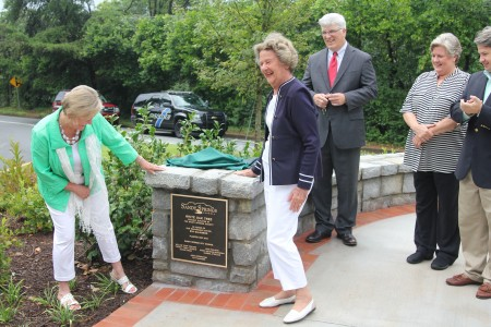 Former Sandy Springs Society president Valerie Love, left, inspects a plaque in honor of Mayor Eva Galambos, right, as Council members Chip Collins, Diane Fries and Gabriel Sterling look on.