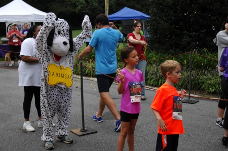"""Ahimsa the dog (actually organization executive director Maya Gupta in costume.), Bethany Patsios, center, and brother brother Ethan Patsios watch for the Patsios' father, Jordon, to complete the """"Wag and Walk"""" fundraising run on Aug. 24 at Lenox Park in Brookhaven."""