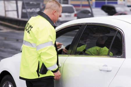 Police Lt. Brandon Gurley checks a driver's license during the city's first day of patrolling the streets with their own force. Gurley responded to a domestic dispute on Buford Highway, and handled a red-light runner during his first day as a Brookhaven law enforcement officer on July 31.