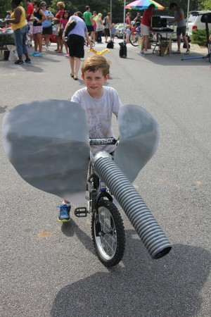 "Will Starling, riding his elephant bike, won the prize for ""most creative"" entry in the parade of vehicles that opened the Brook Run trail in Dunwoody on Aug. 3. Photo by Joe Earle."