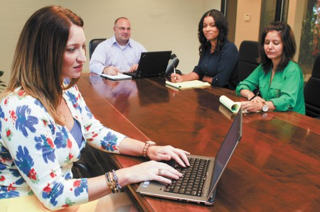 Employees of GT Software, a global information technology company with its headquarters in Sandy Springs, meet in the conference room. Left to right, Heather Frogge, director of accounting, Tim Sacklyn, financial analyst, Deborah Reed, accounting clerk, and Ellie Soleymani, marketing manager.  GT Software received $6,284 in economic incentives to locate in the city of Sandy Springs.