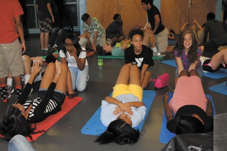 From left, Micah Hurt, Alayna Orr and Lindsey Starr help their friends do sit ups during a Leaders Club meeting.