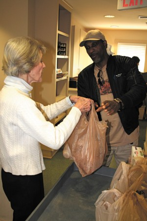 Buckhead Christian Ministry volunteer Caroline Haynes distributes bags of food to a BCM client.