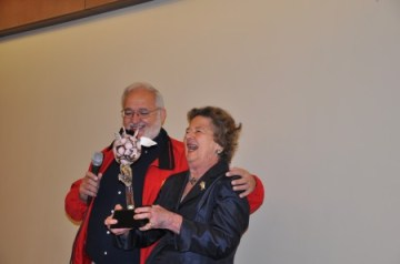 Councilman Tibby DeJulo presents Mayor Eva Galambos with a flying pig statue during a Dec. 8 going away party in Sandy Springs.