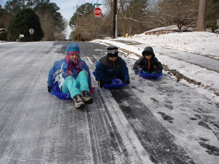 From left to right, Malena Shipley, 9, Fernando Reyes, 6, and Jesus Reyes, 4, employed the tops fo recycling bins to take advantage of the ice and snow for downhill rides on Jan. 29. Photo by J.D. Moor