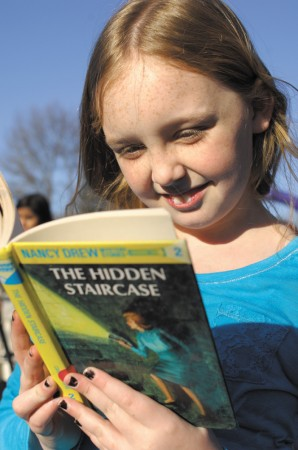 """Arwen Coy, selects a book to read from the """"little library"""" in Briarwood Park."""