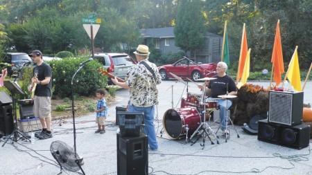 From left, David Schurer, Gary Hunnicutt and David Selden perform at Hillsdale's annual Oktoberfest block party as Santiago Sickler dances along.