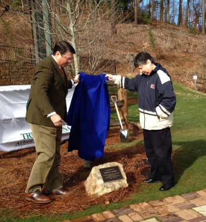 Sandy Springs Mayor Rusty Paul, left, and Barbara Evans unveil a plaque marking a tree planted on Feb. 21, Arbor Day, in memory of her husband, David Evans, who died in December.